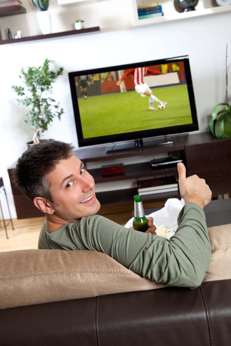 Man watching football with a beer