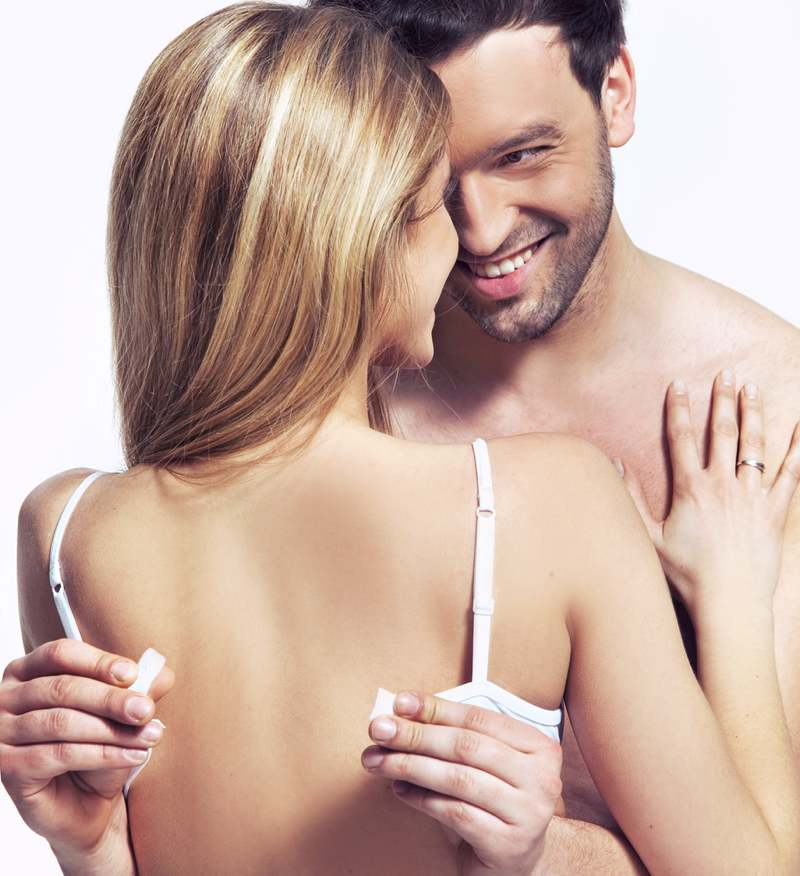 cheeky man removing woman's bra