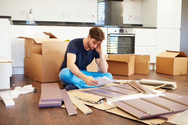 frustrated man building flat pack furniture