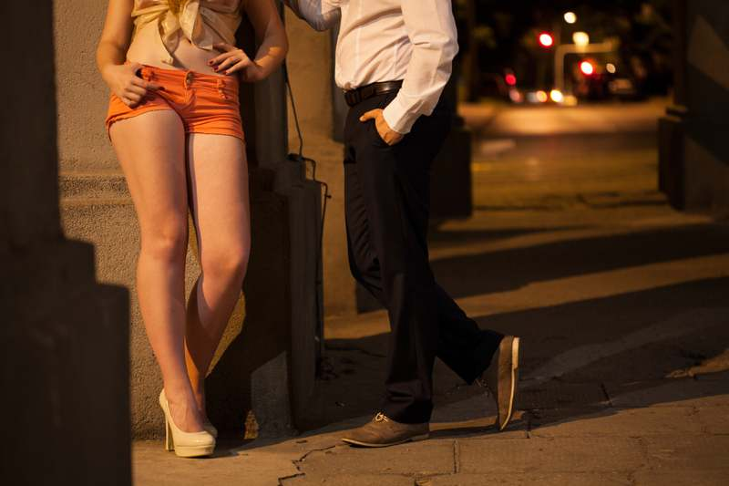 man talking to prostitute