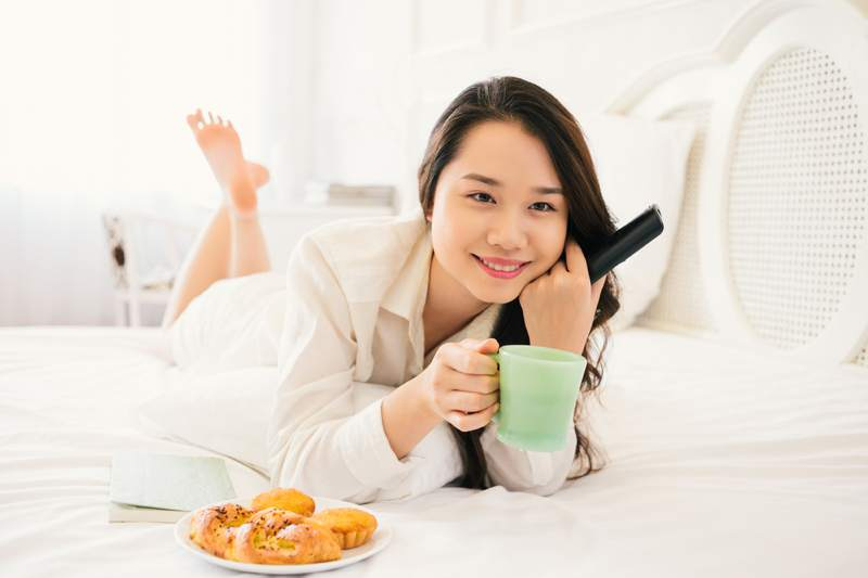 woman eating breakfast and watching tv