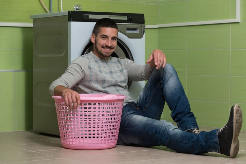 Handsome man washing clothes