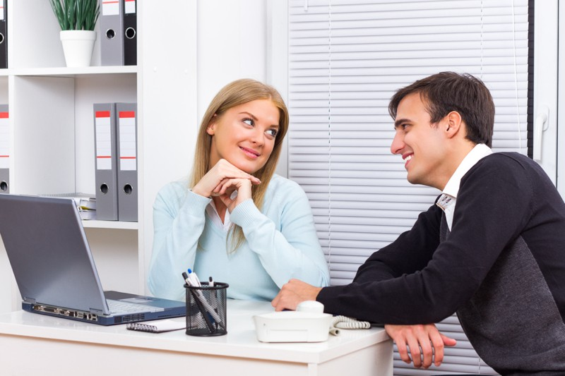 Young woman is flirting with her boss at work
