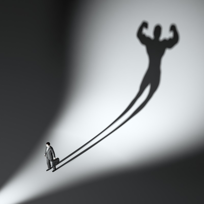 Business man casting a shadow of an athlete